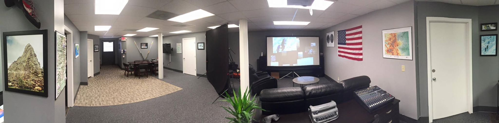 Interior photo of the Blind Endeavors Foundation Headquarters. Consists of a couple black reclining couches, large projection screen and adventurous photos on the wall.