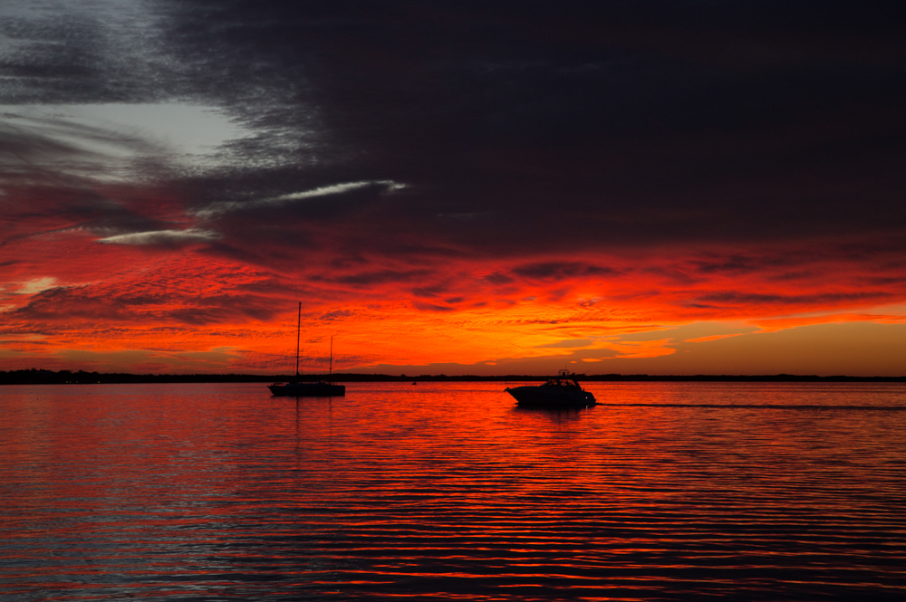 A sailboat sits anchored in the distance with a sky exploding in orange and red like a hovering fire as the sun sets on the horizon. The fierce oranges and reds reflect off of the gentle waves of the ocean.