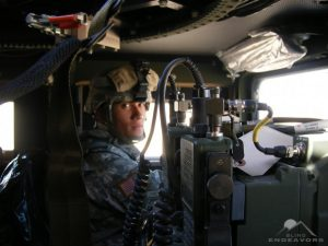 Steve Baskis posing for a photo dressed in camouflage and sitting in a humvee