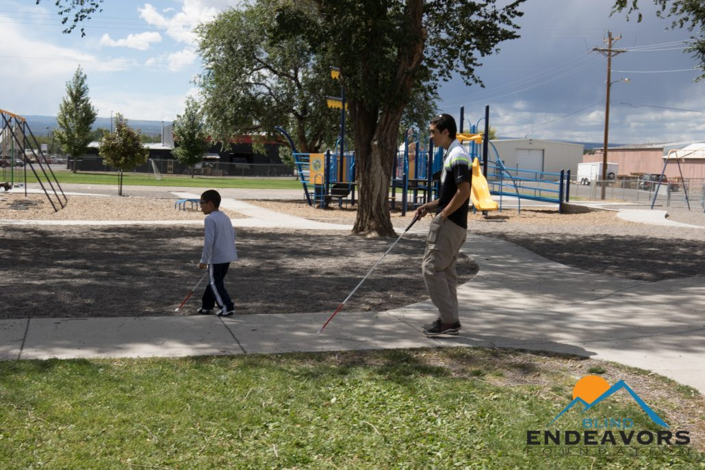 A first grade child uses his cane to guide Steve through his playground at school.