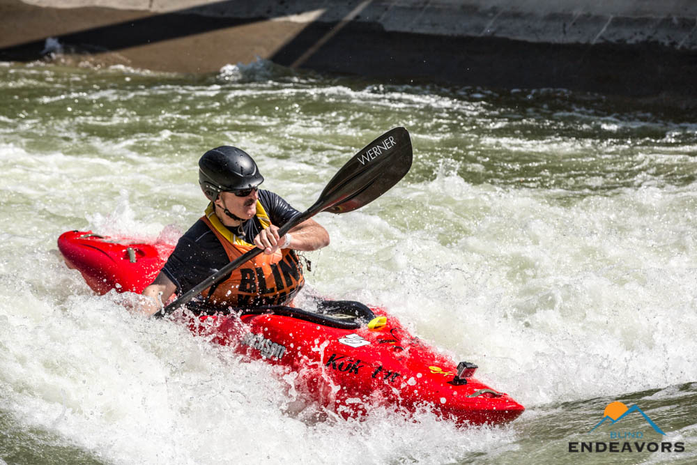 Lonnie Bedwell surfs a wave in a whitewater kayak