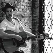 Photo of Cody Marlowe Leaning against a brick wall with a guitar in hand.