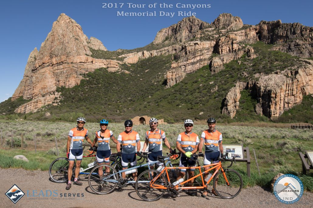 Group photo of all the riders of Tour of the Canyons in front of various rock formations.