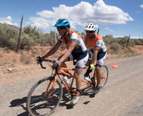 Anne Ryan and Nate Gorham ride on an orange tandem bicycle along a dirt road. Cumulus clouds scatter the sky behind them with scrub brush emerging from the red dirt.