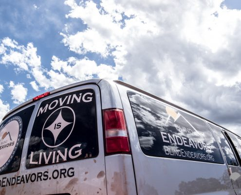 Blind Endeavors Van with Moving is living and compass on back window. Cumulus clouds scatter the sky behind the van.