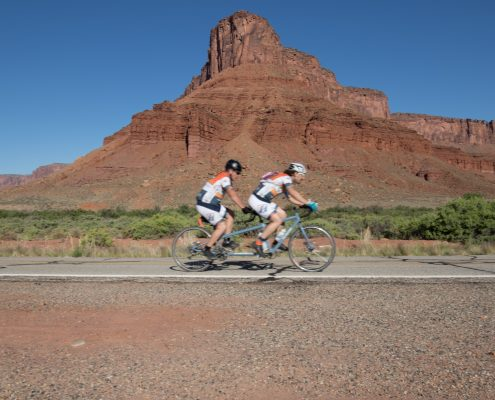 Two men on a tandem bike ride by with a large rock spire in the background